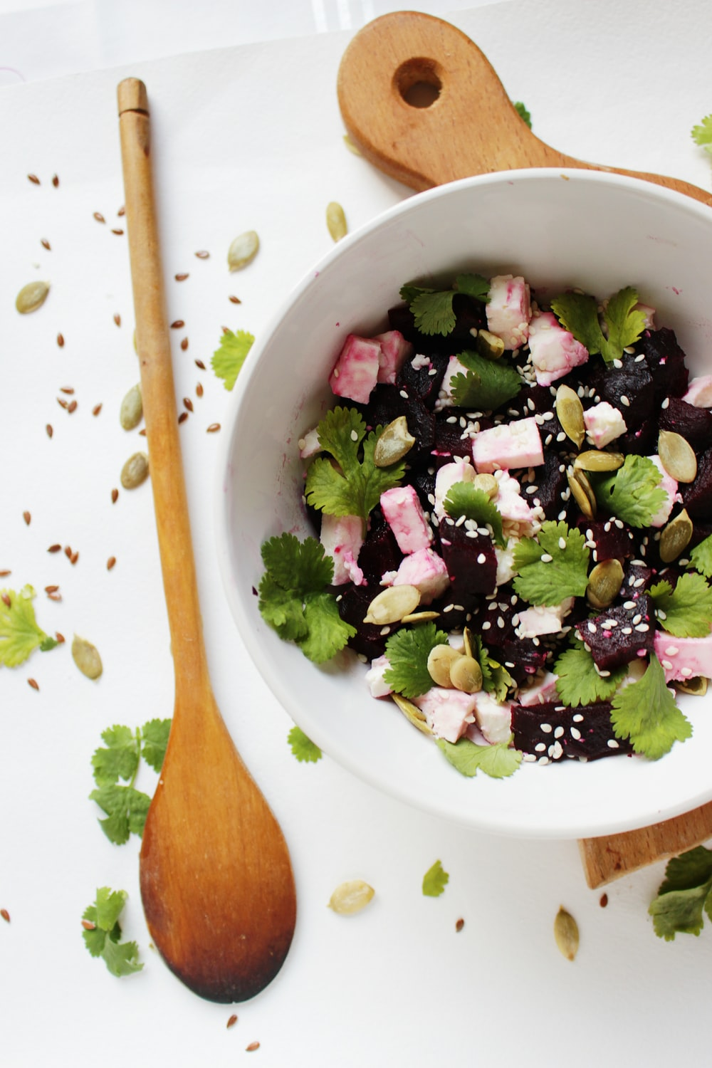 vegetable salad topped with sesame seeds in round white ceramic bowl beside brown wooden ladle