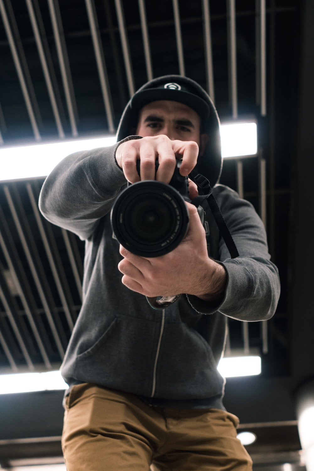 low angle-view of man holding DSLR camera