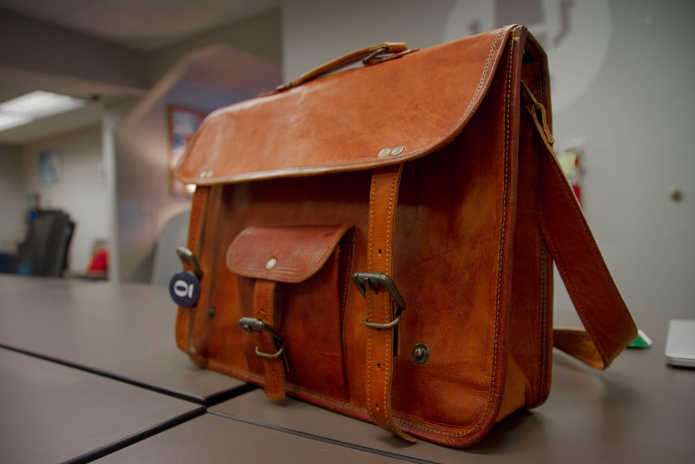 closeup photo of brown leather crossbody bag