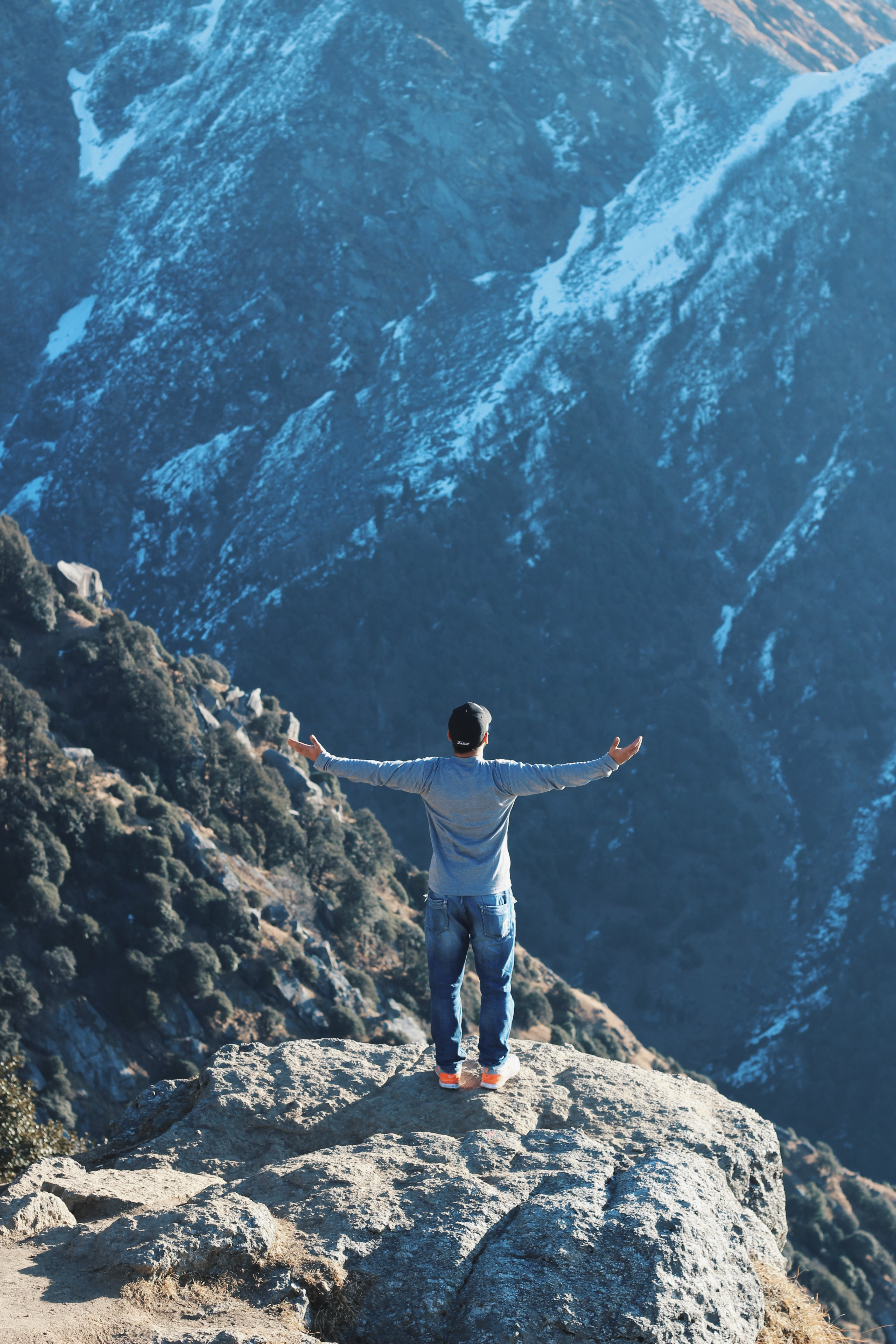 person standing on rock mountain while raising his hand sideways