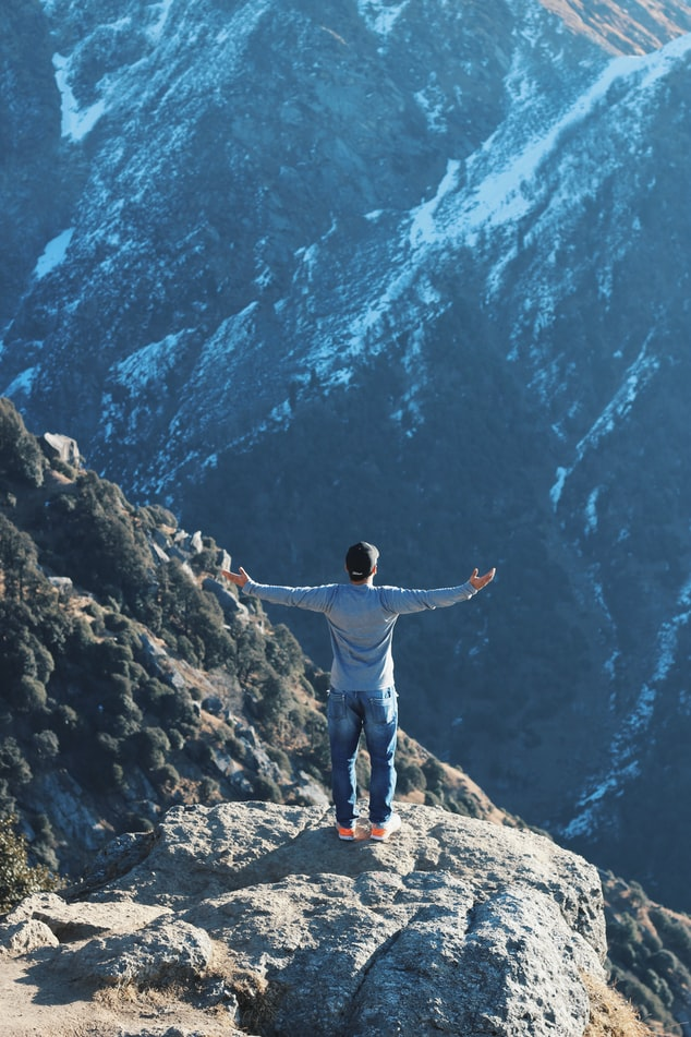 A guy standing on a rock mountain in Triund Trek