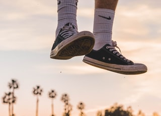 person wearing black low-top sneakers jumping high under white sky