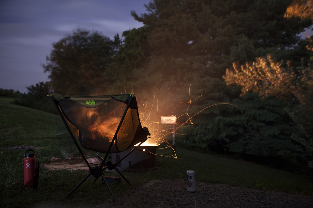 camper chair beside firepit beside trees