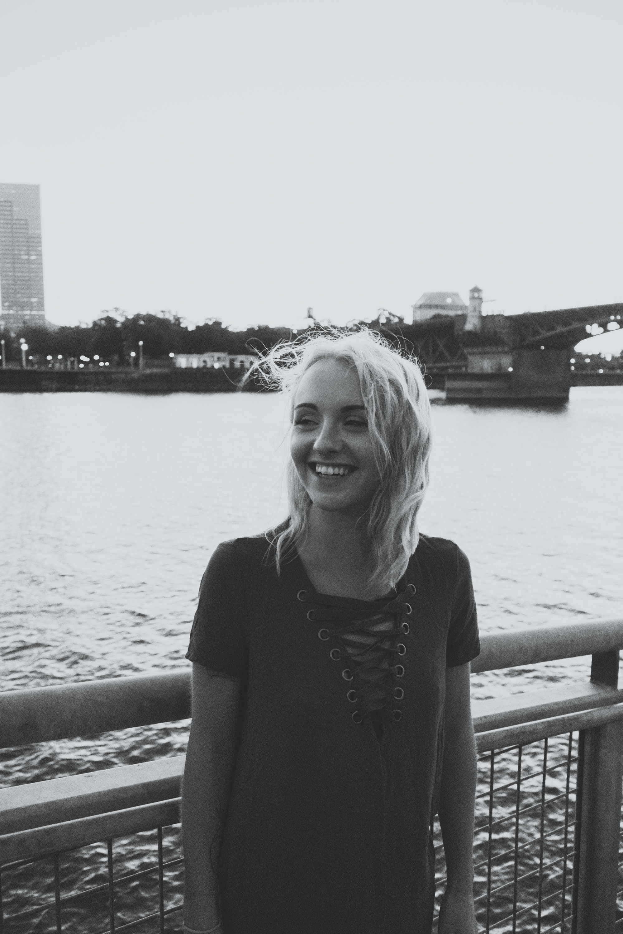 grayscale photo of smiling woman standing near fence above body of water
