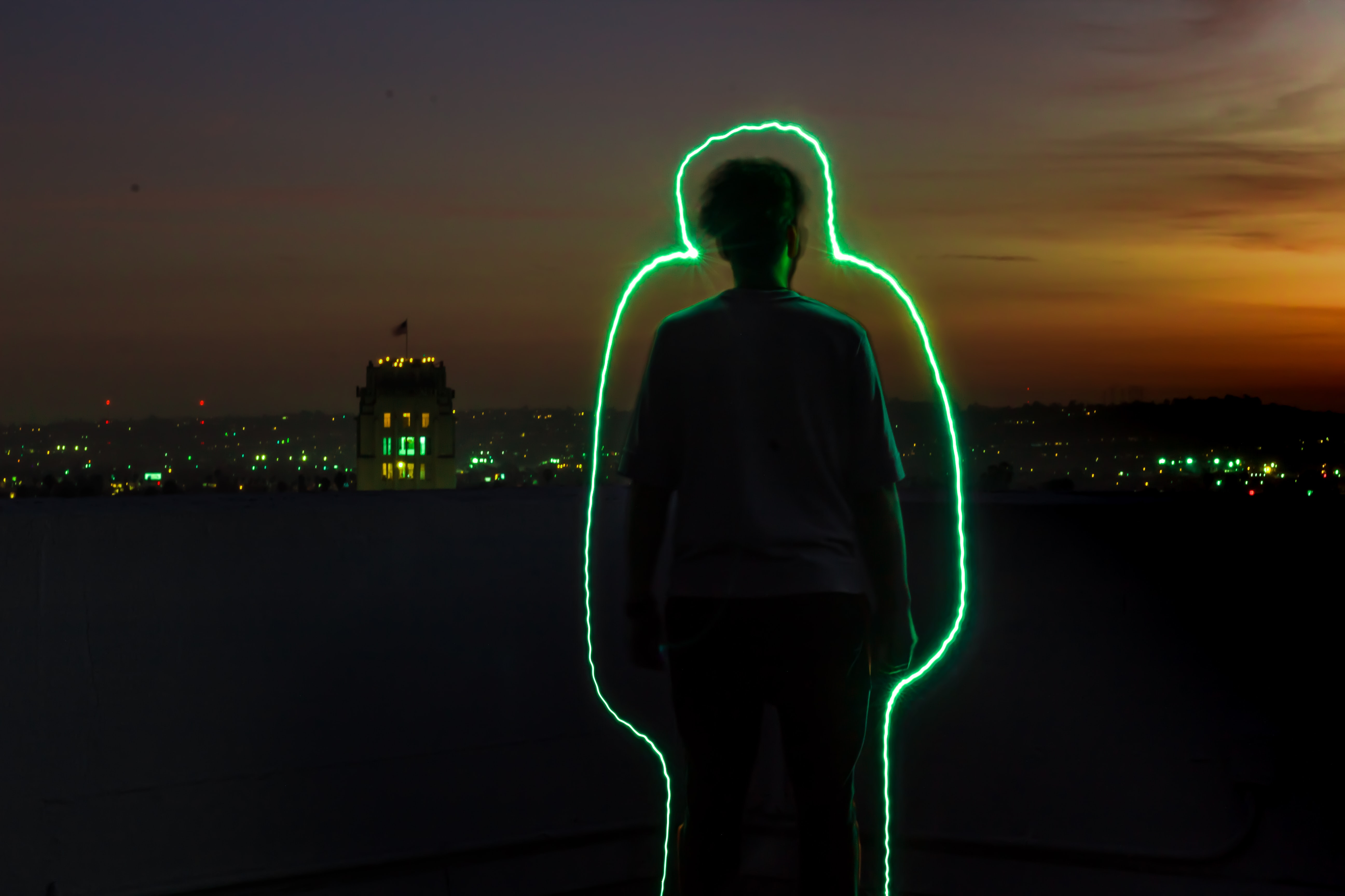 silhouette of man standing with green neon outline during sunset