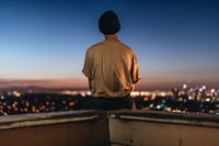 person sitting on rooftop ledge during nighttime