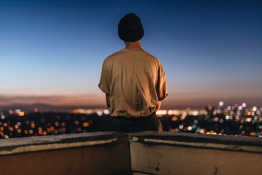 Person Sitting On Rooftop Ledge During Nighttime Photo