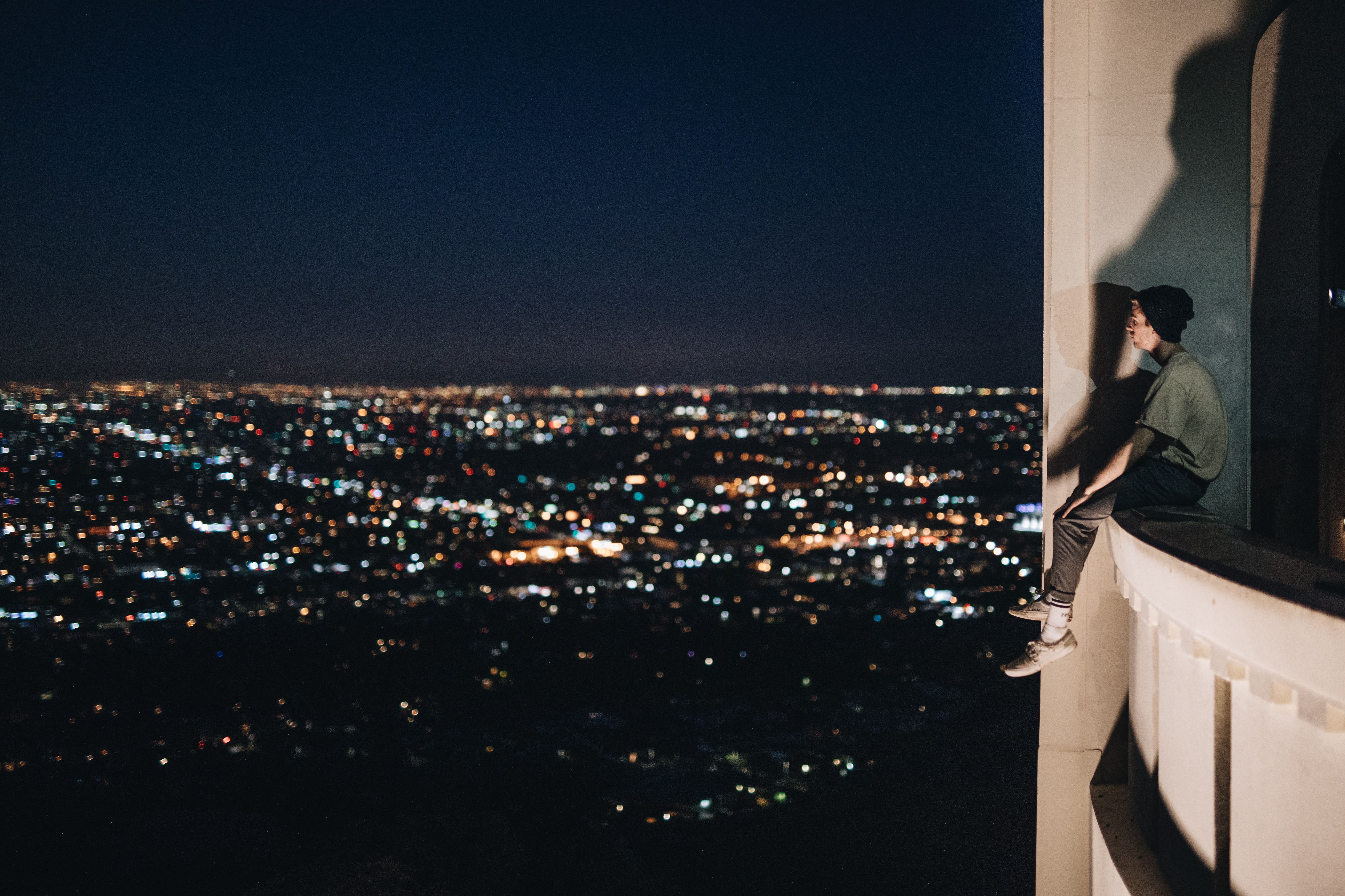 man sitting on building balcony during nighttime