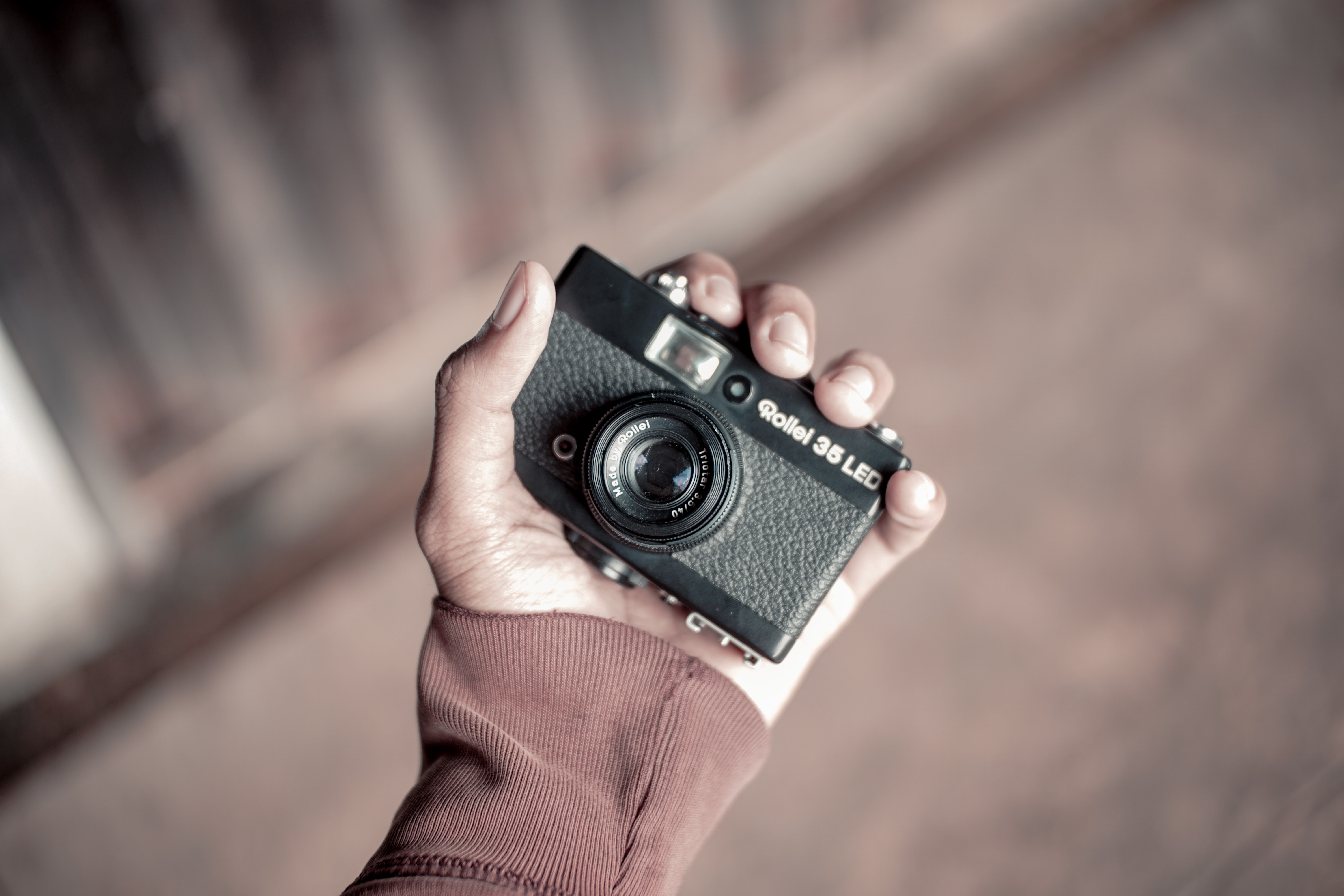 person holding black and gray point-and-shoot camera