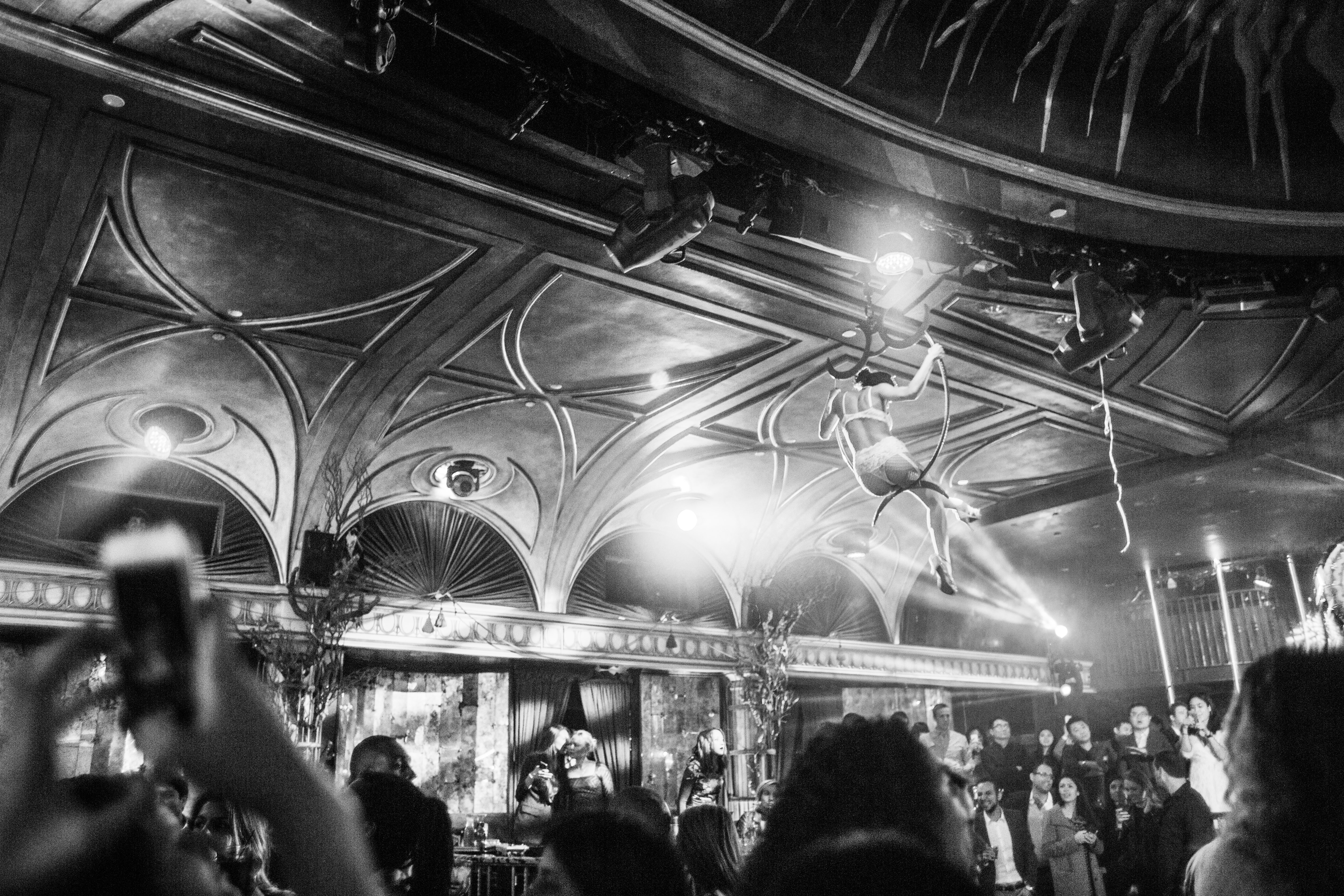 grayscale photography of woman hanging near ceiling surrounded by crowd