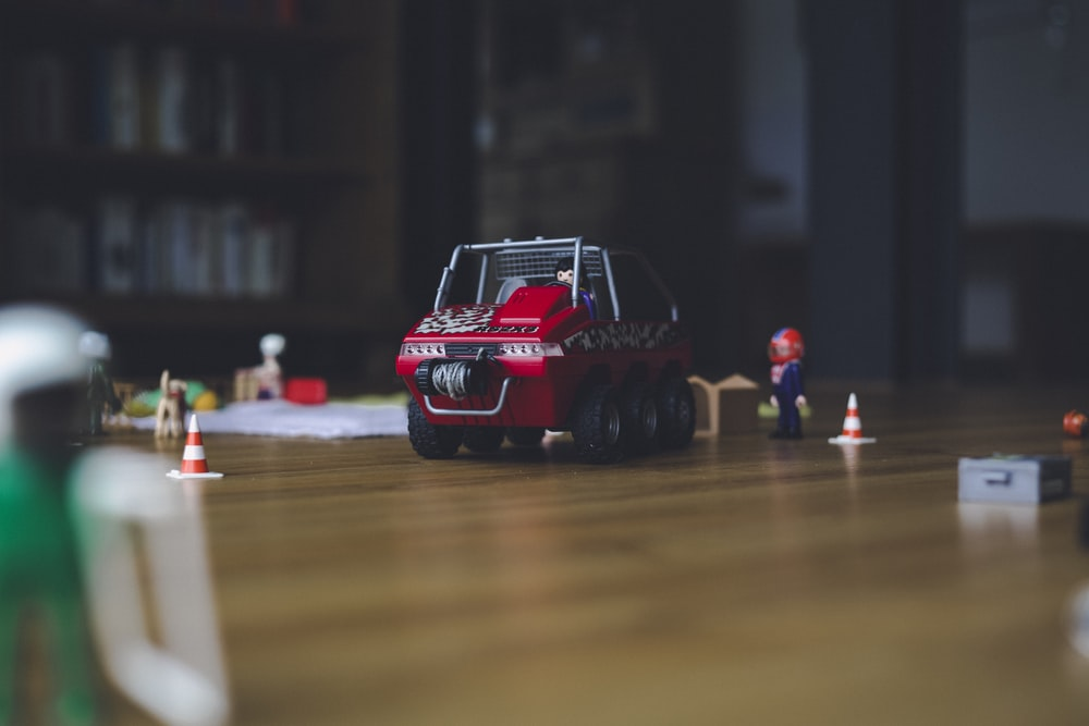 red and black truck toy on floor