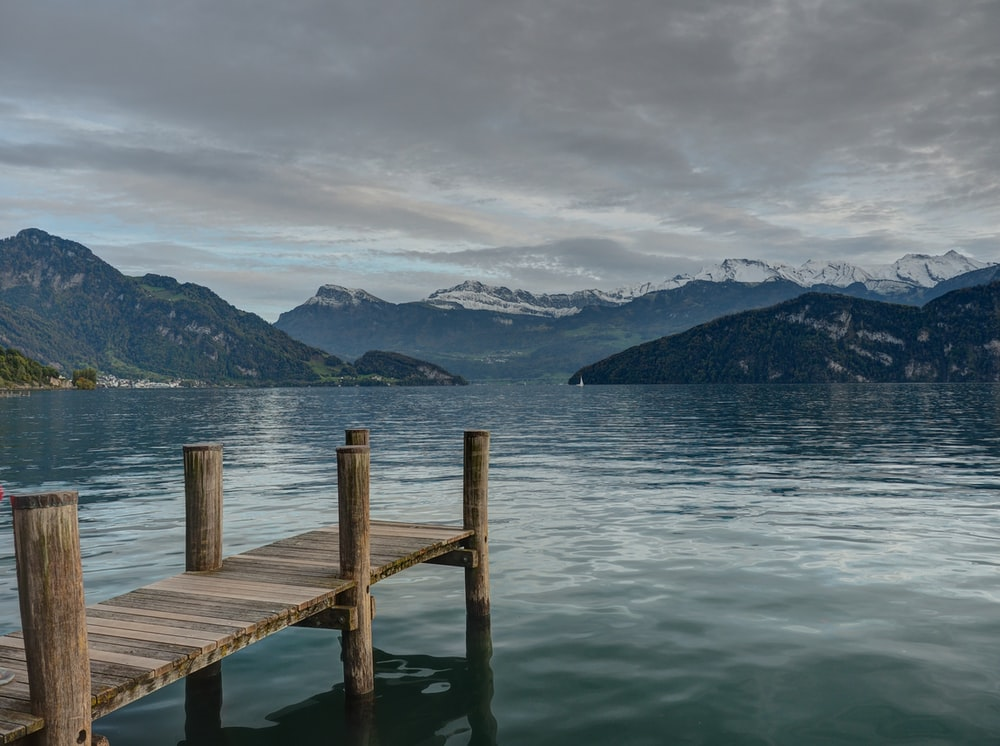 closeup photo of brown wooden dock facing mountain and calm body of water