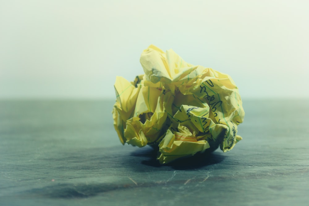 crumpled yellow ruled paper on gray panel
