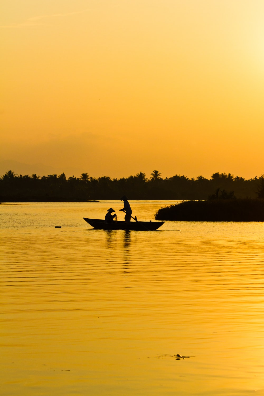 photography of silhouette of two person's in sitting and standing in boat