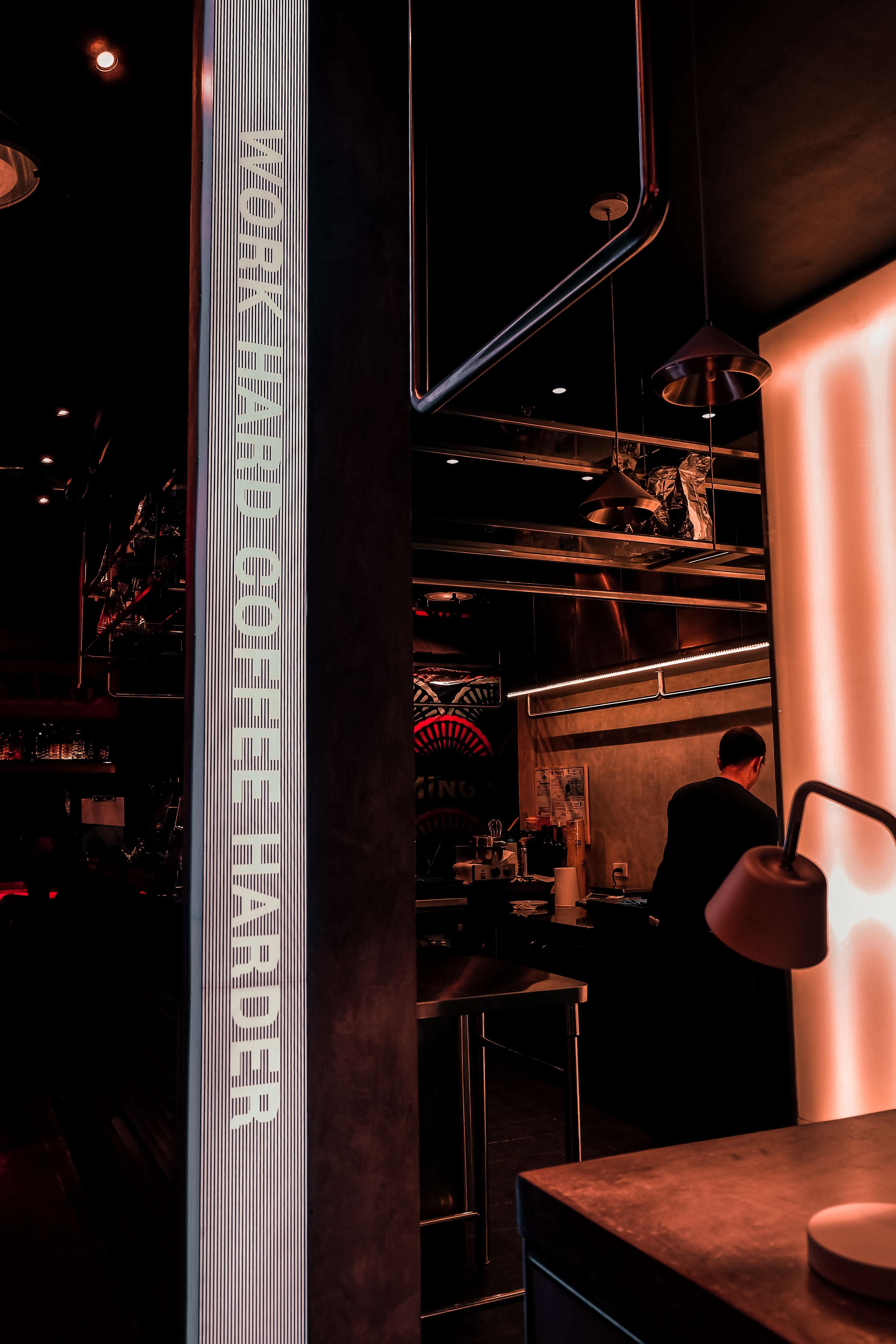work hard coffee harder signage near man standing inside the bar