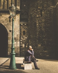 man sitting on bench beside post lamp