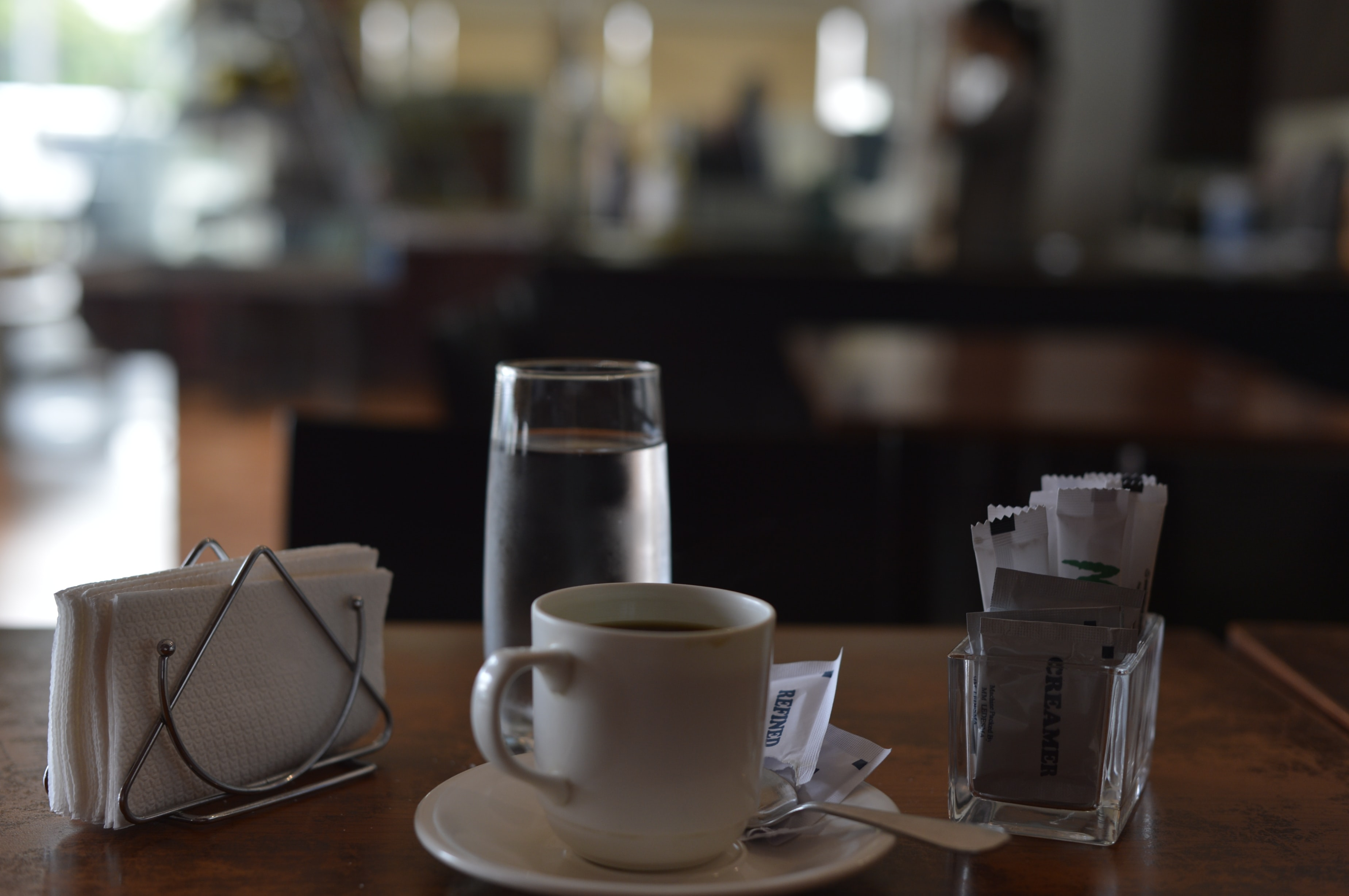 selective focus photography of teacup beside tissue and drinking glass on top of table