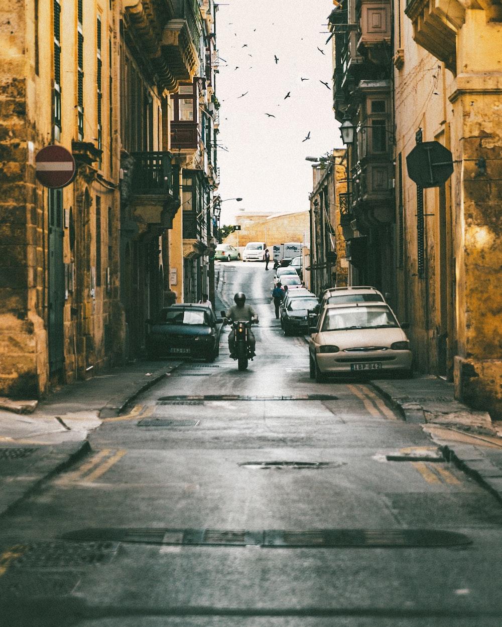 man riding motorcycle passing through buildings