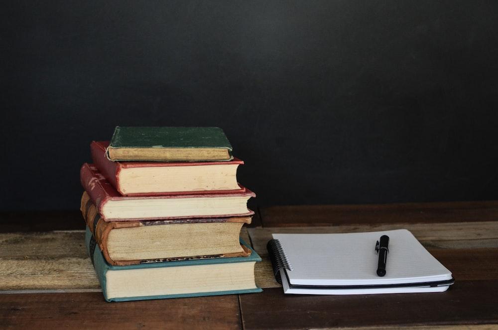 pile of books beside white printer paper and black ballpoint pen