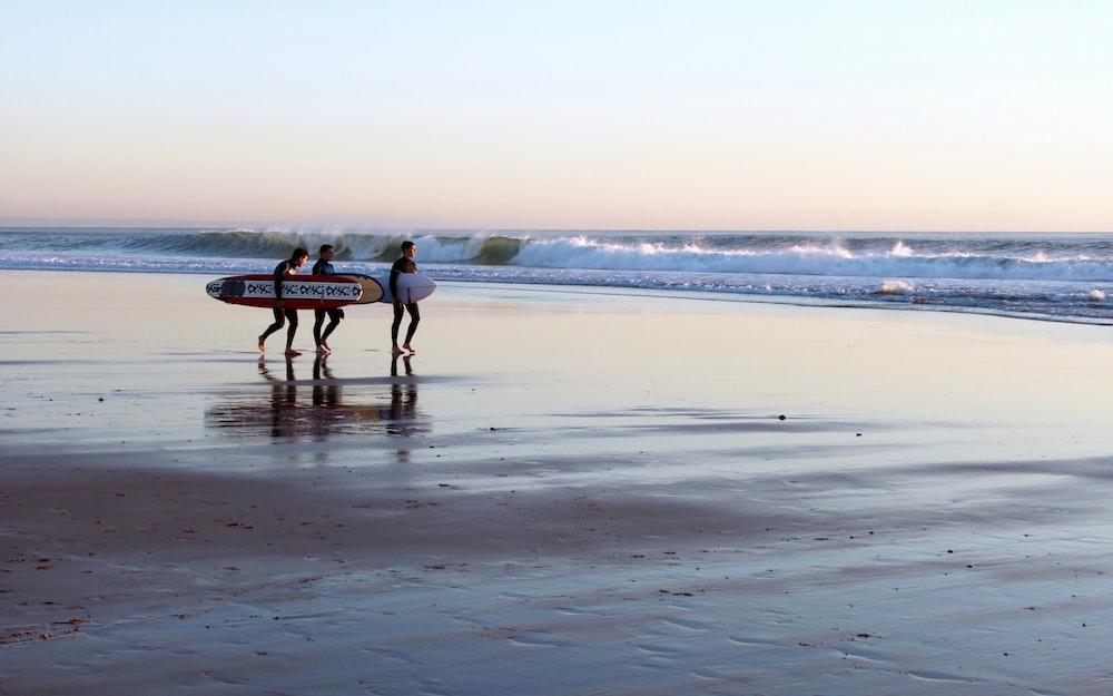 three man holding surfboard while walking on seashore