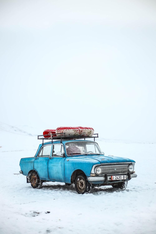 blue sedan on snow ground