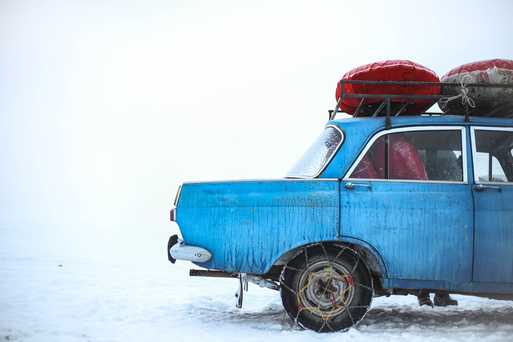 blue sedan with chain on tire parking on snowfield at daytime