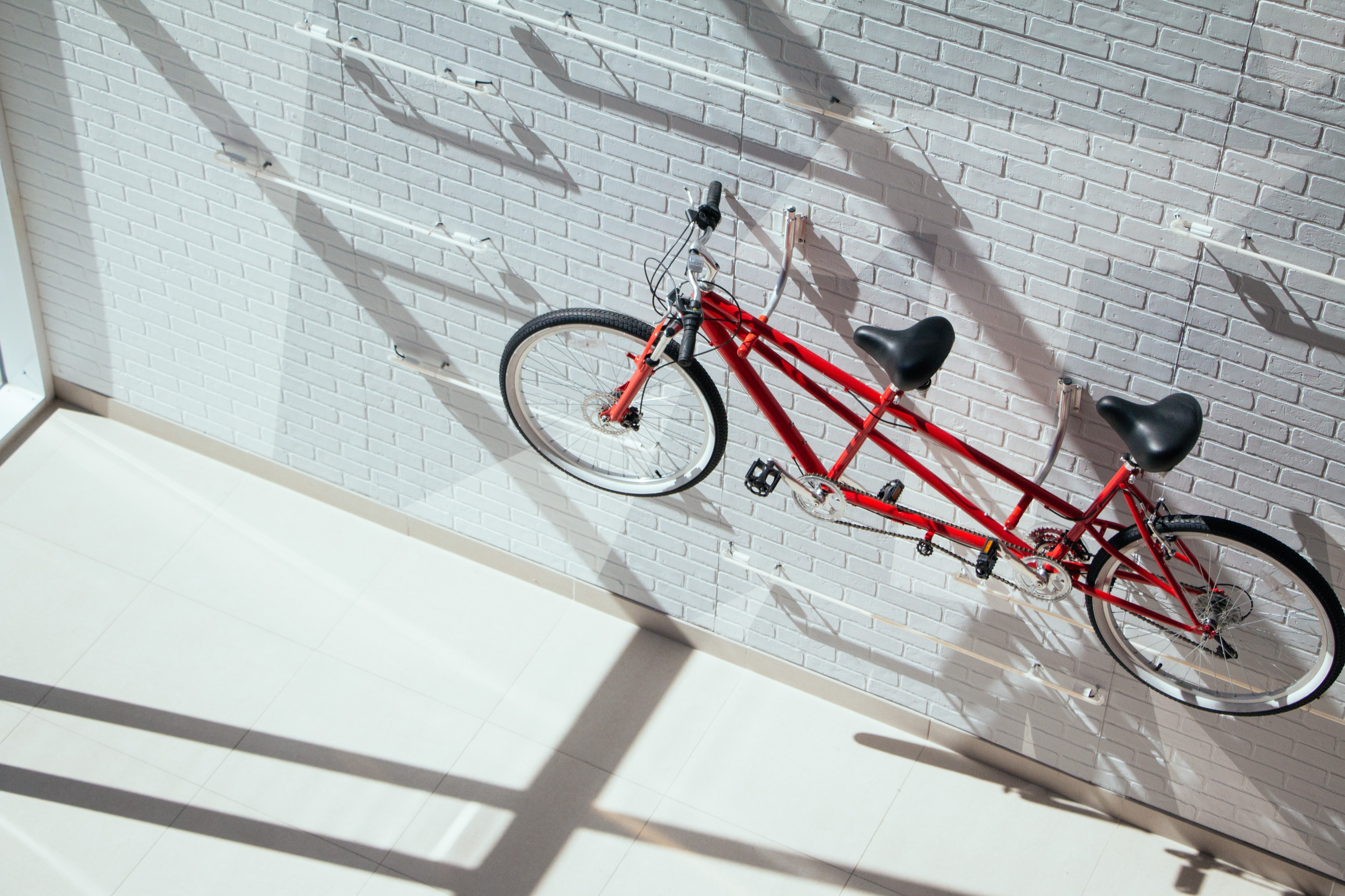 red tandem bicycle hanging on wall