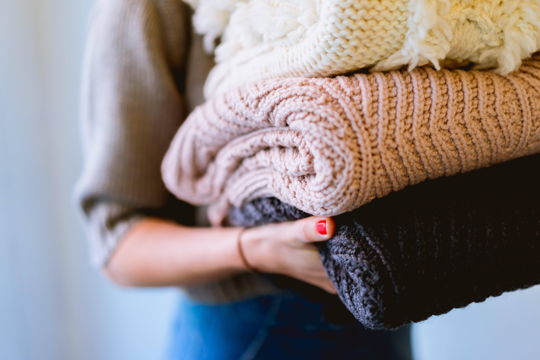 Person trägt drei bunte Pullover auf dem Arm