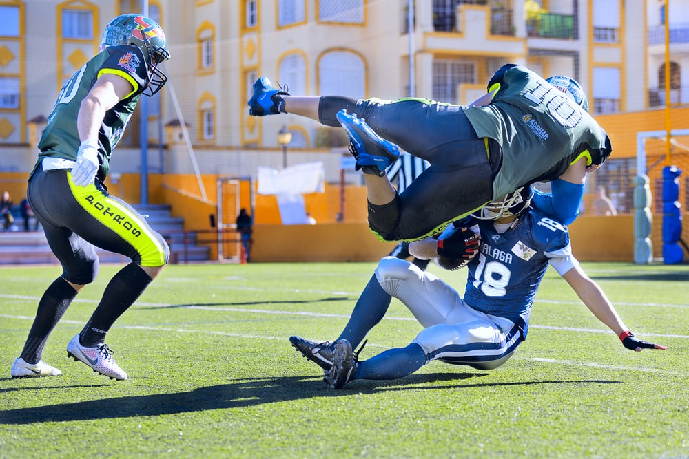 football player in green jersey tackling player in blue jersey