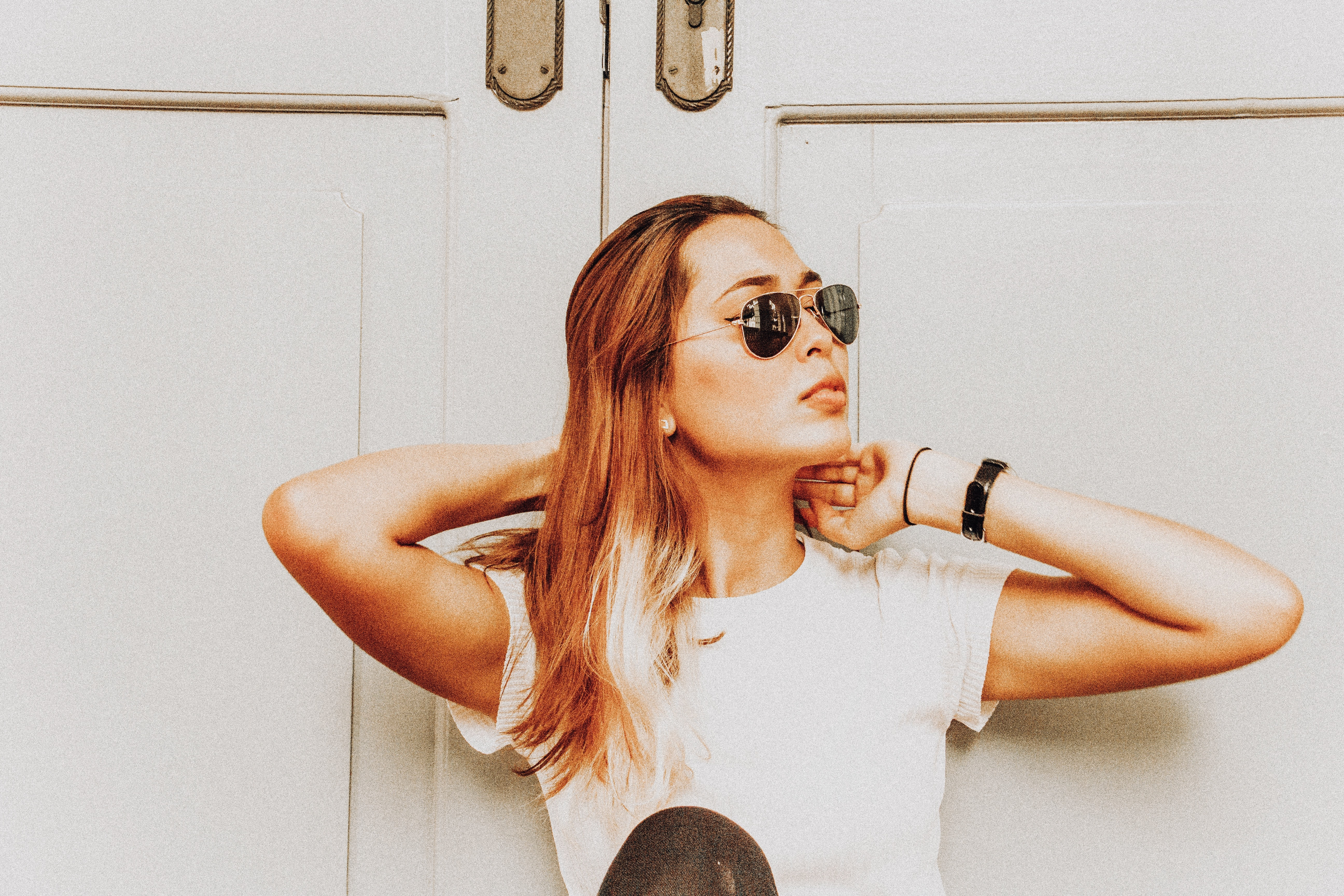 woman wearing black sunglasses standing in front of door at daytime