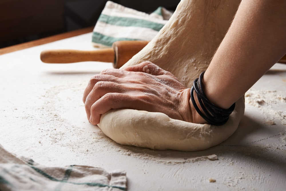 person making dough beside brown wooden rolling pin