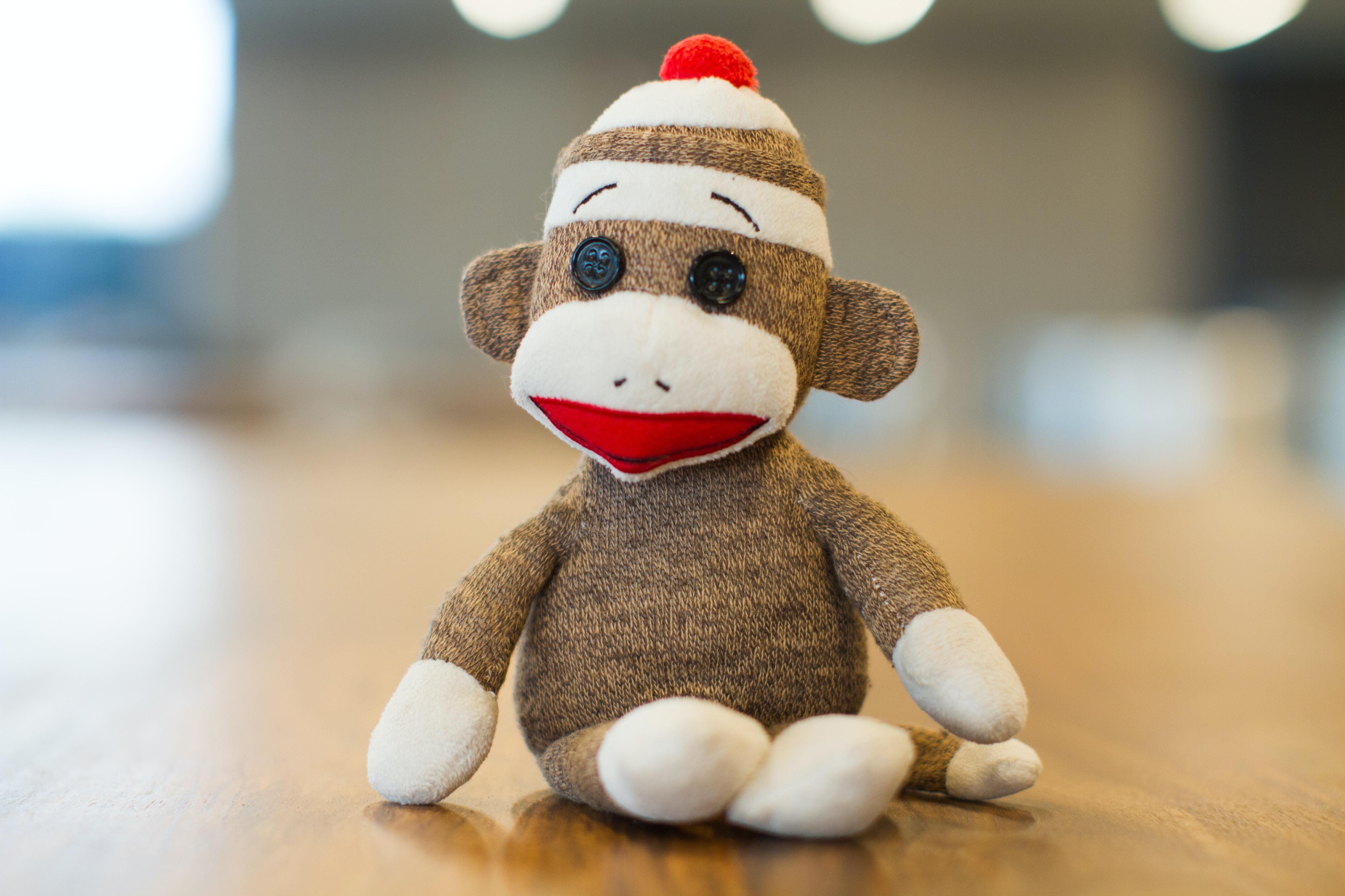 Sock Monkey plush toy on brown panel