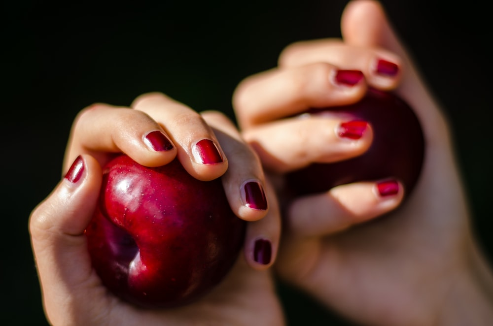 selective focus photography of person holding red apples