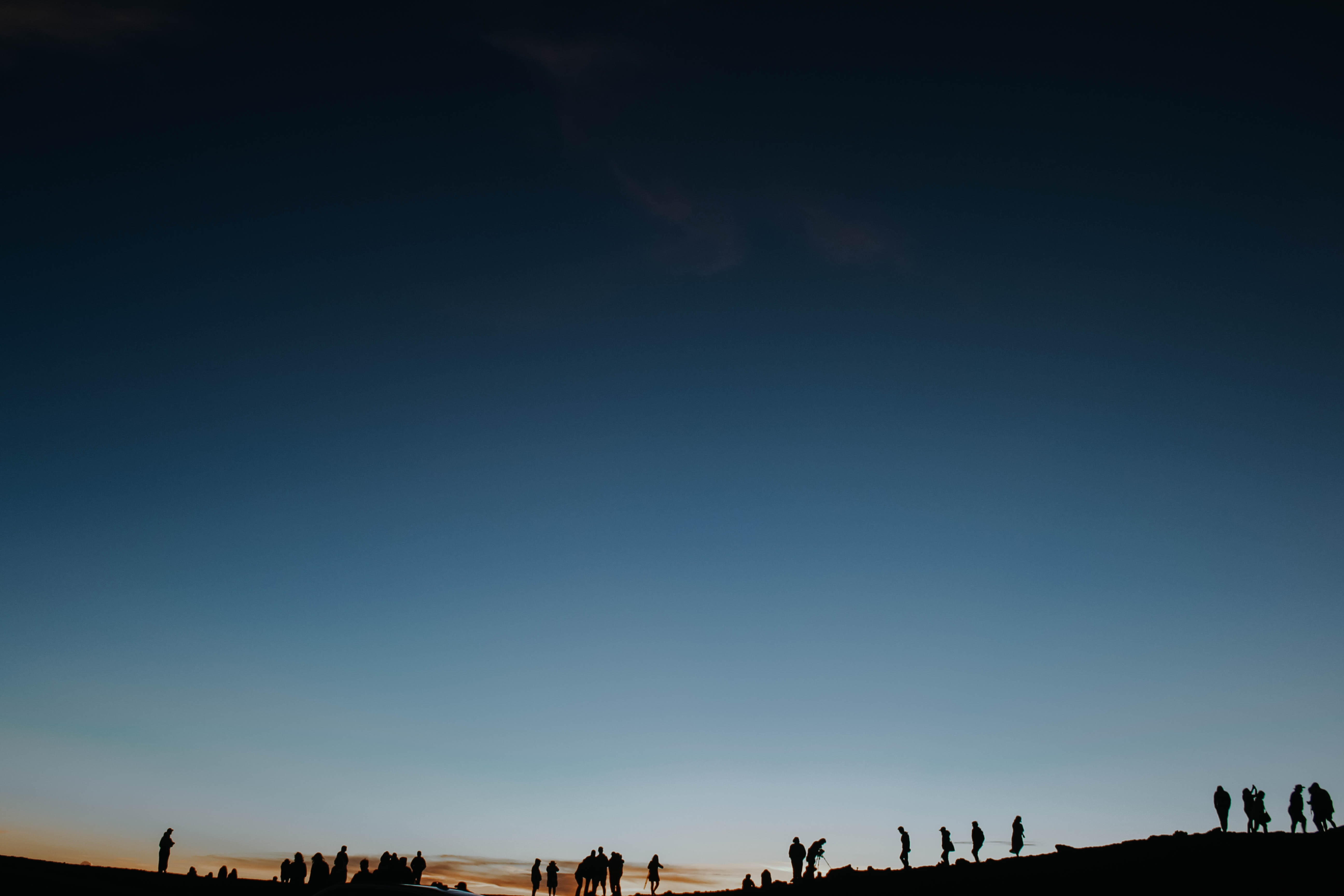 silhouette of people standing in cliff