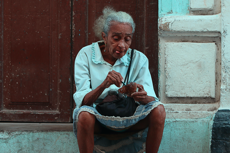 woman sitting on gray concrete ground near brown wooden door