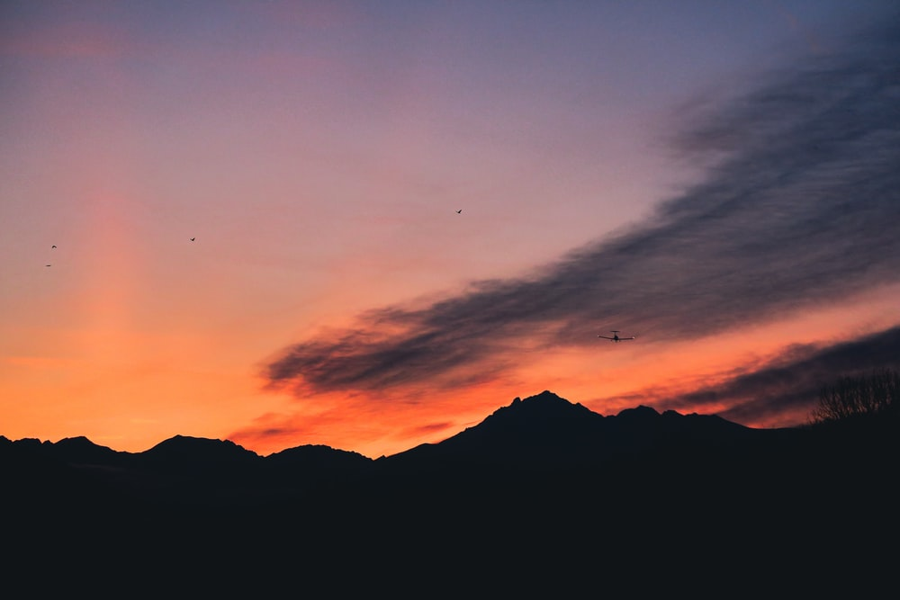 silhouette of mountain under white clouds
