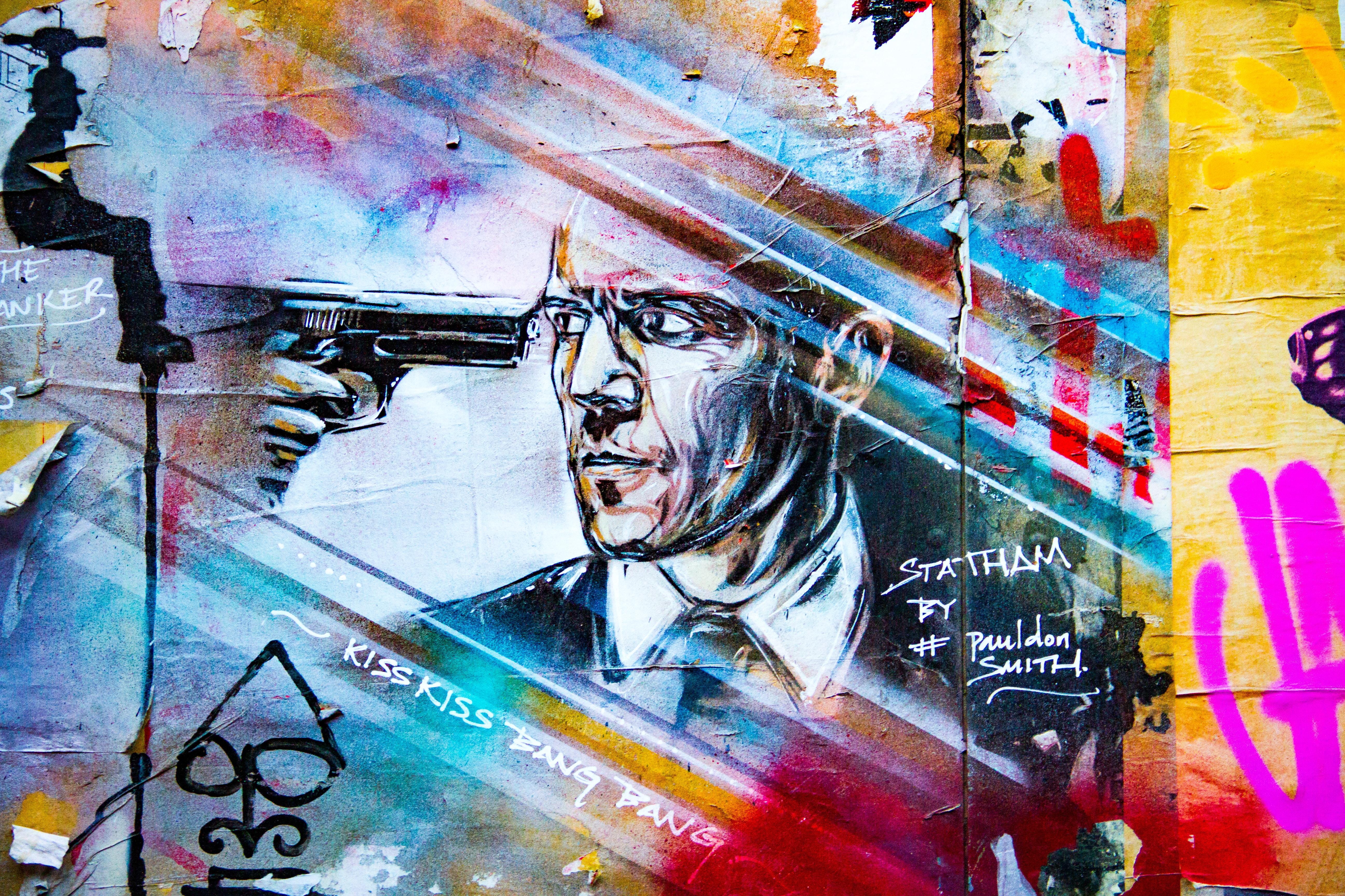 gun pointed on man's eye painting