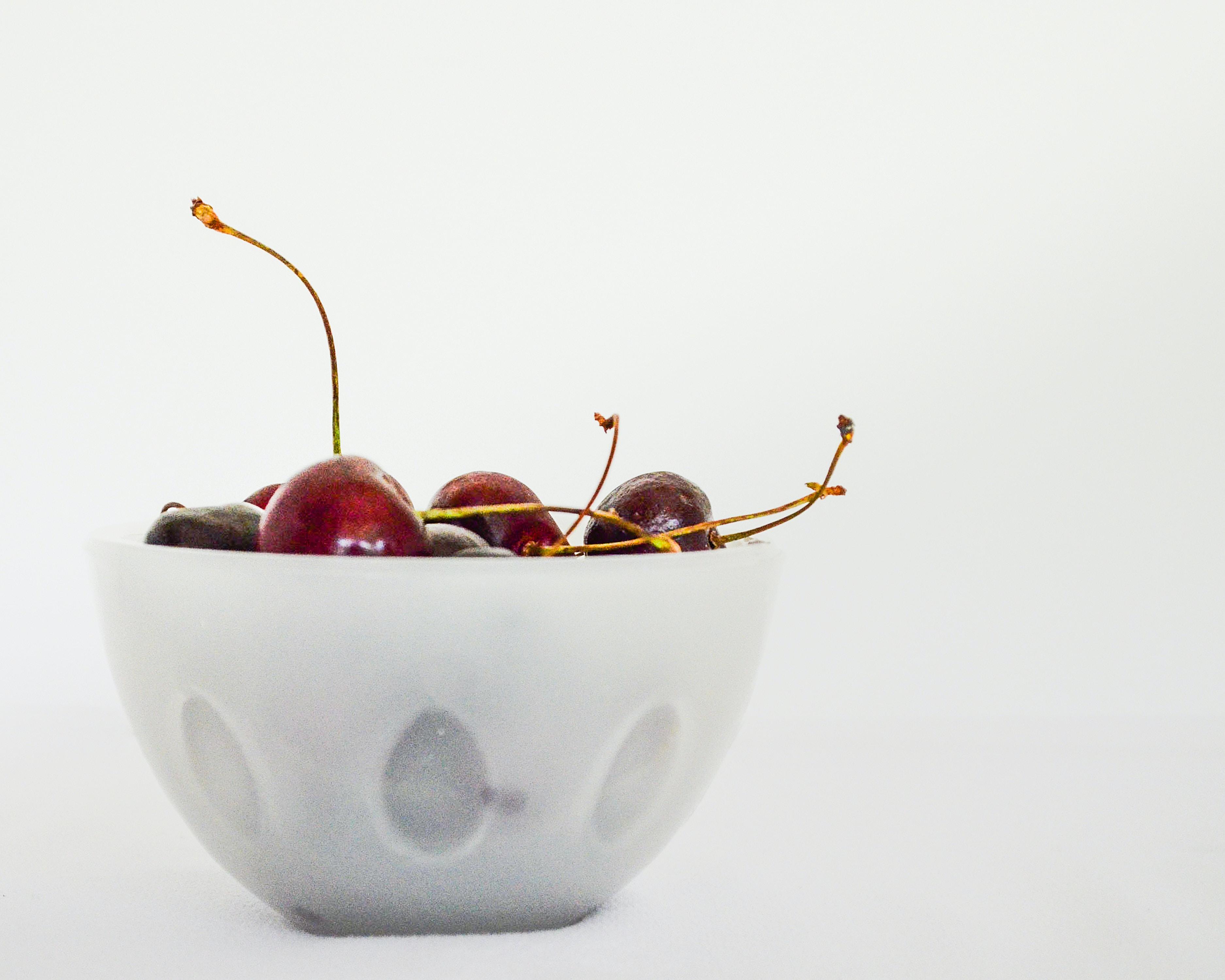 red cherries in white ceramic bowl