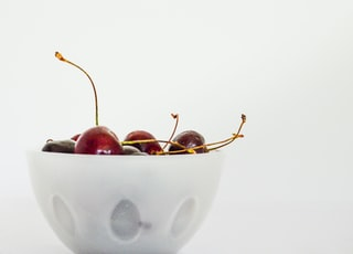 red cherries in white ceramic bowl