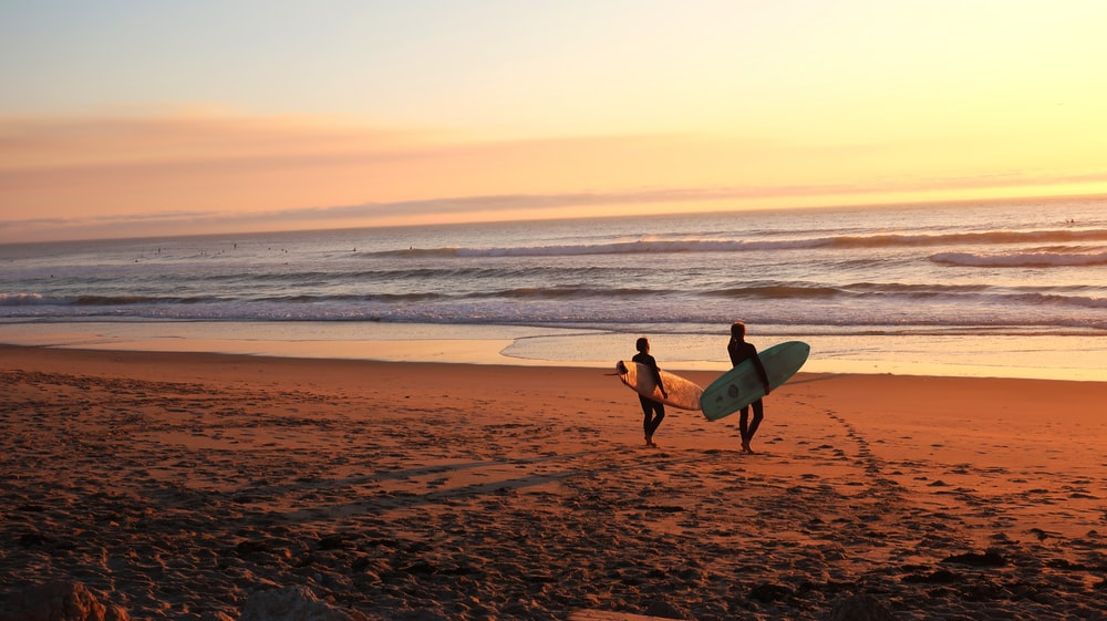 two surfers walking on sand going on water