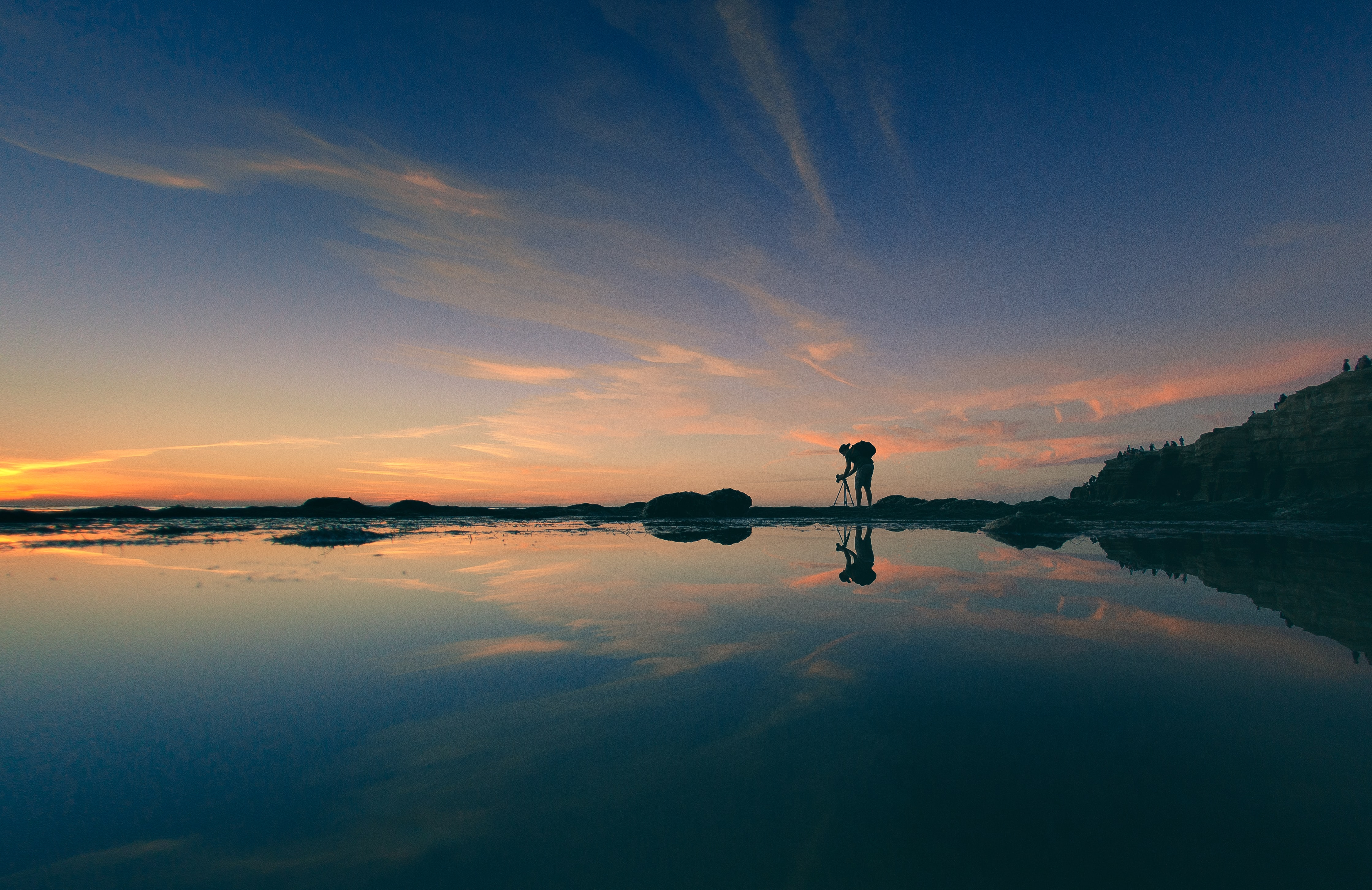 landscape photography of man adjusting camera tripod during golden hour