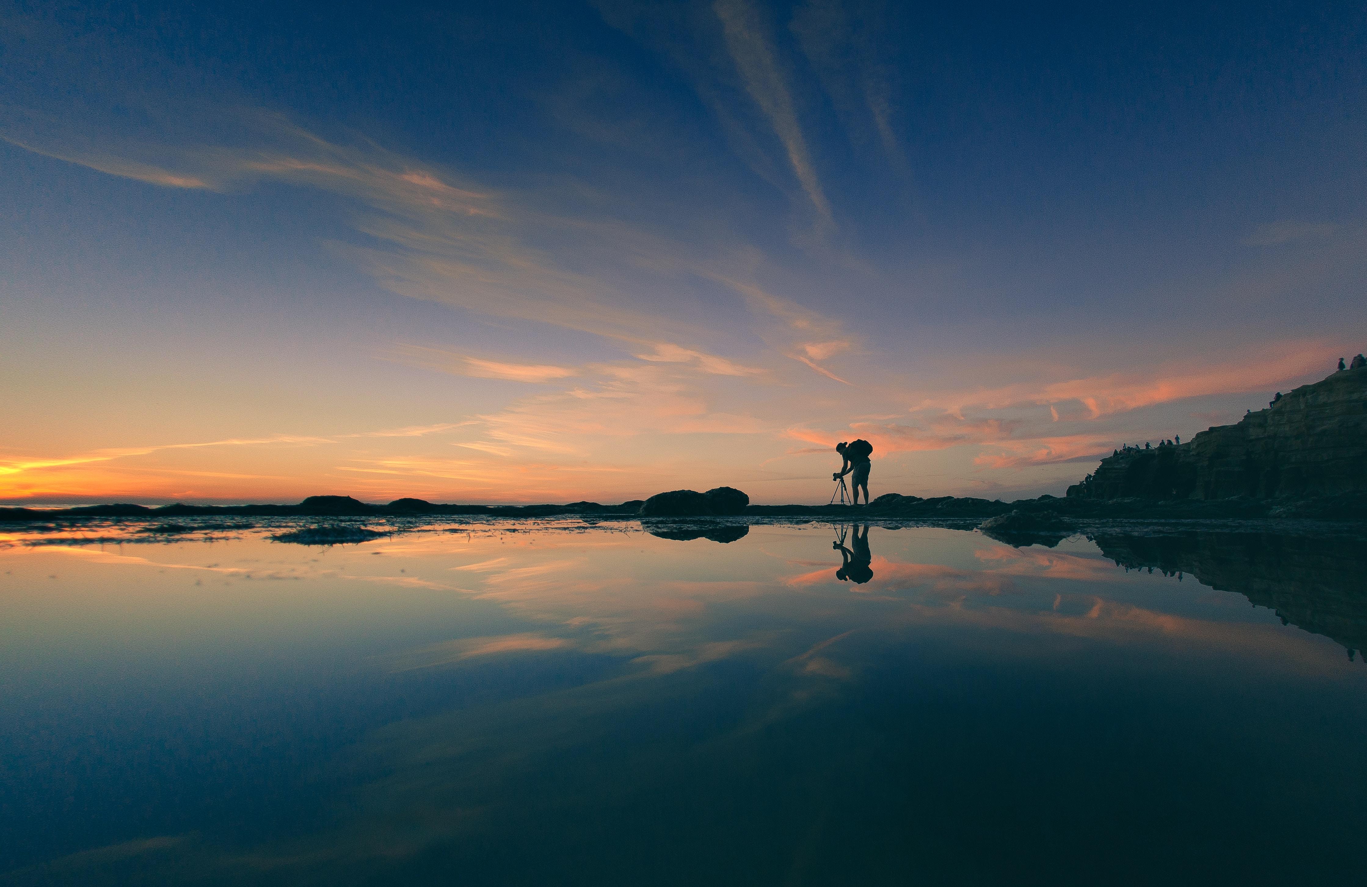 landscape photography of man adjusting camera tripod during golden hour
