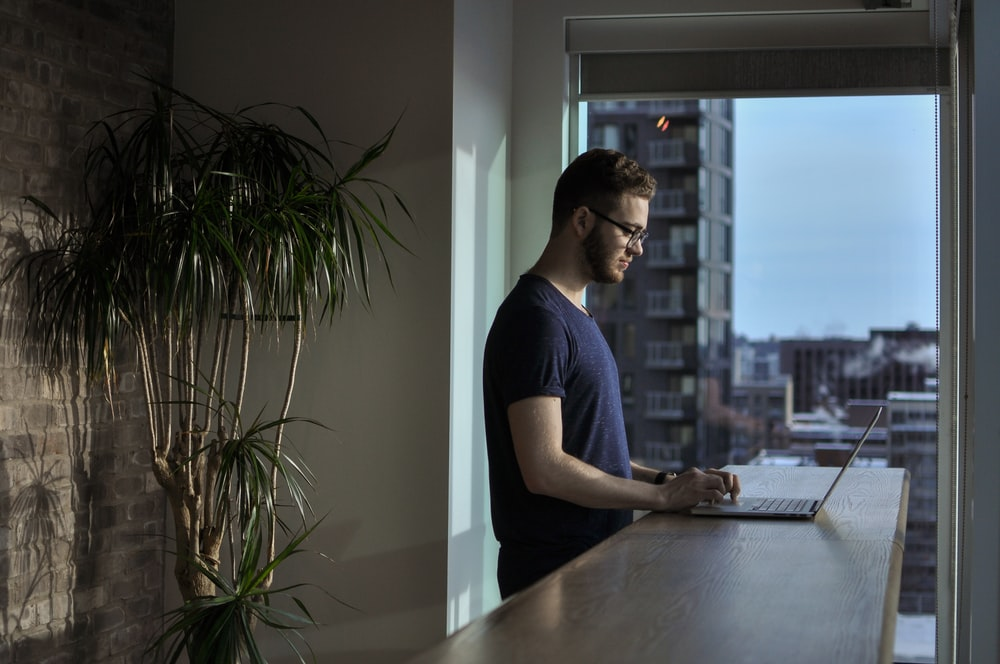 man standing beside table using laptop