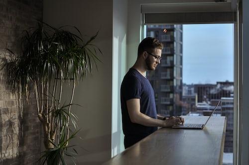 man standing at counter using laptop