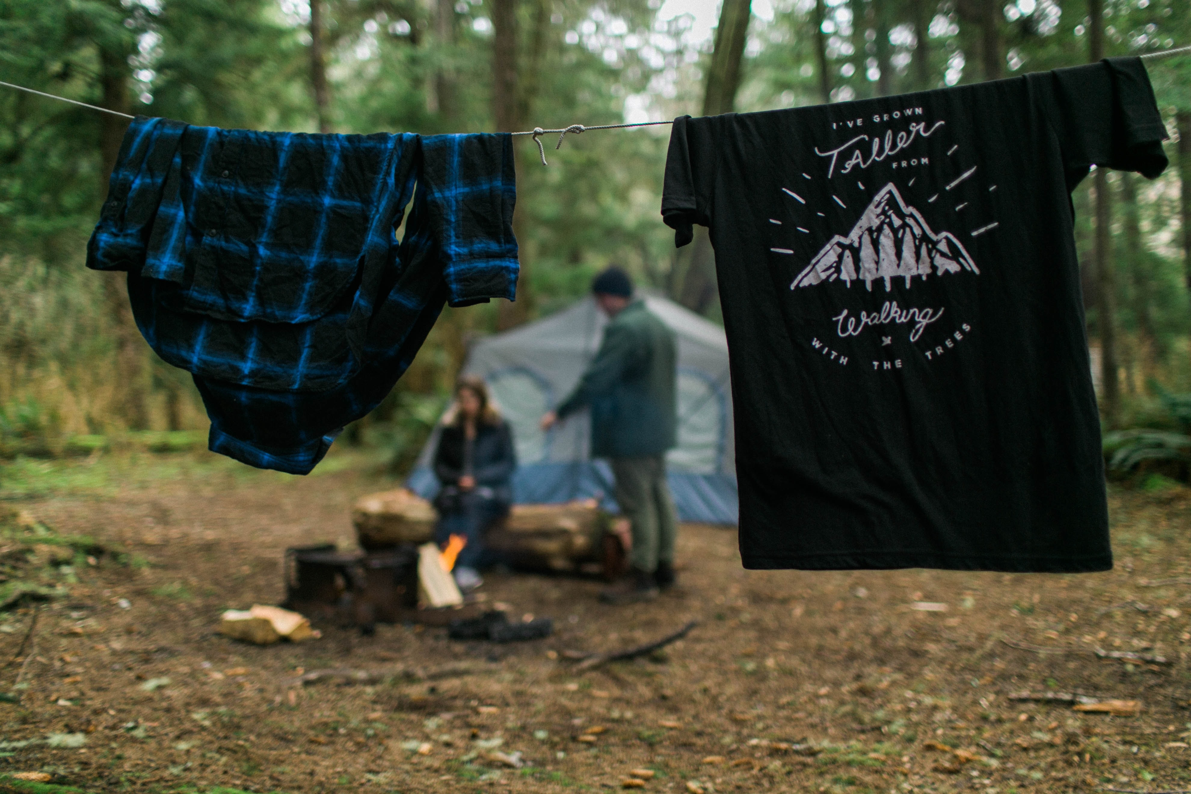 two shirts hanging near woman and man beside blue tent under tall trees