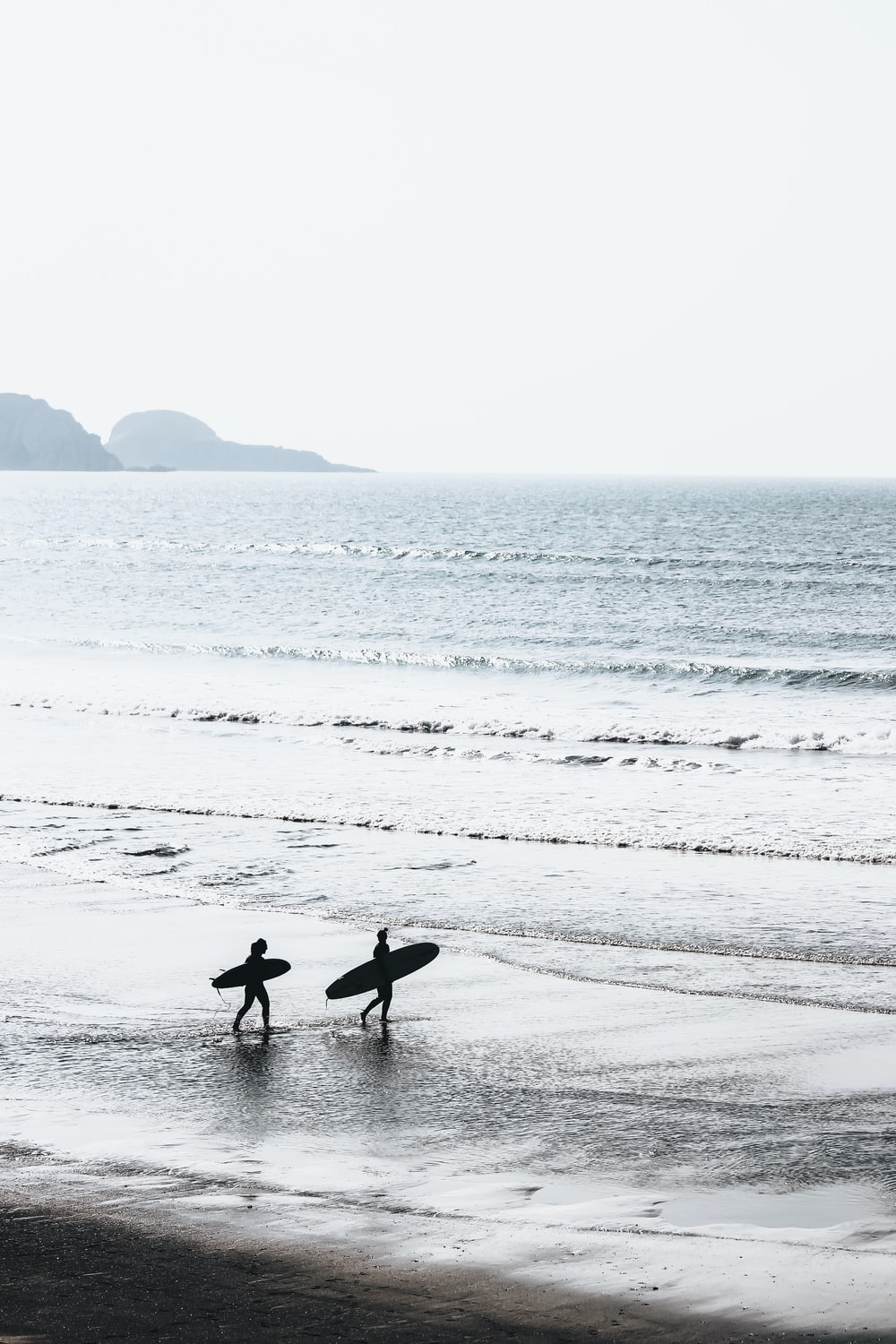 two people carrying surfboards at beach during daytime