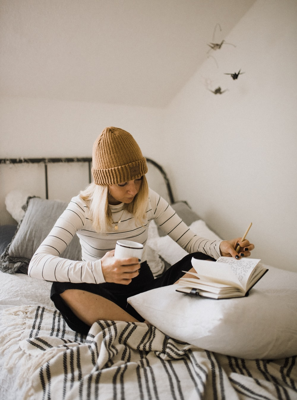 woman in striped shirt sitting on bed while writing