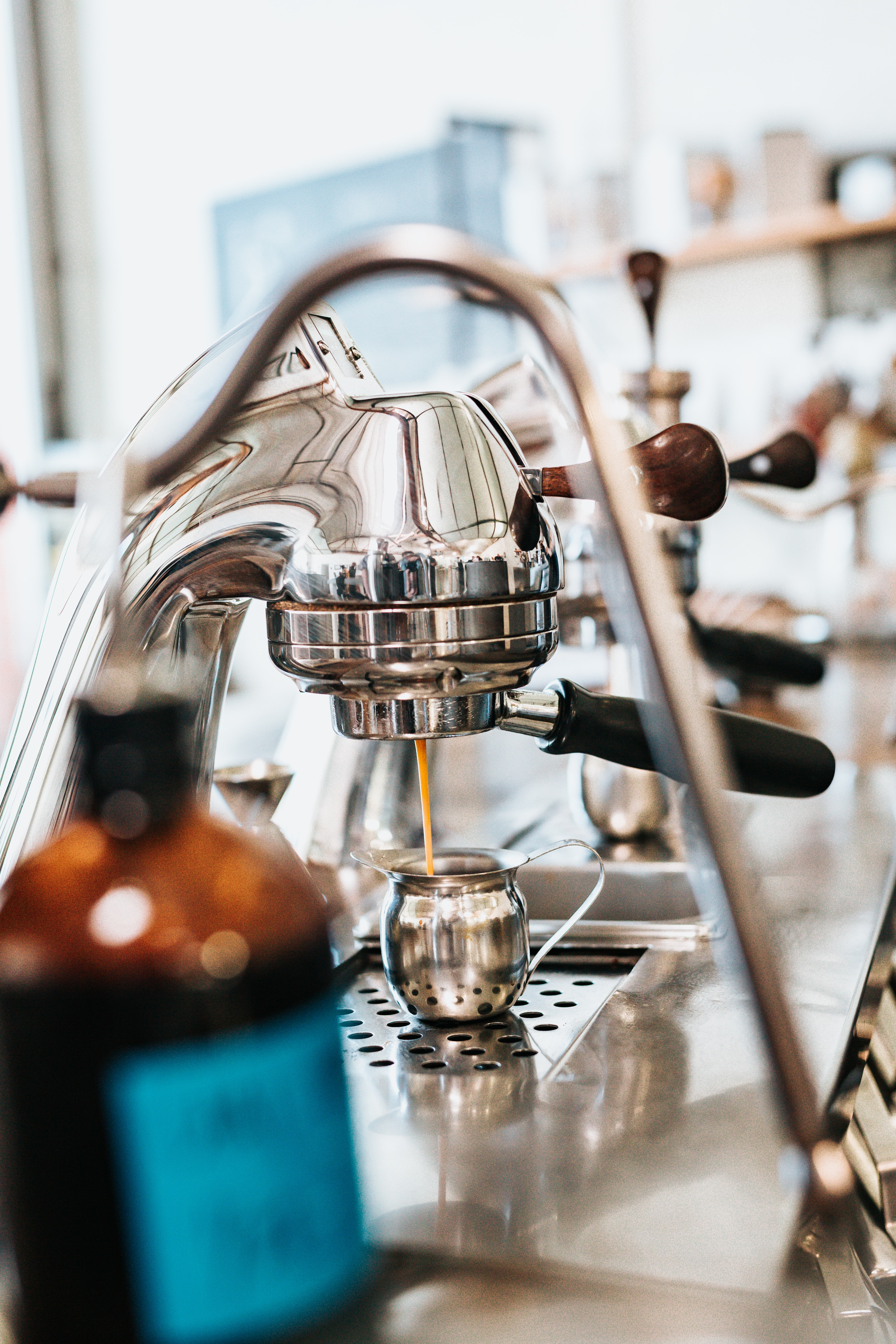 stainless steel espresso maker filling a cup