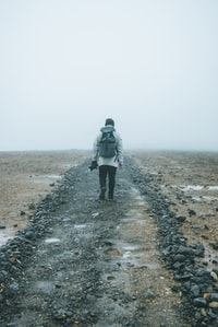 man with backpack walking on brown field