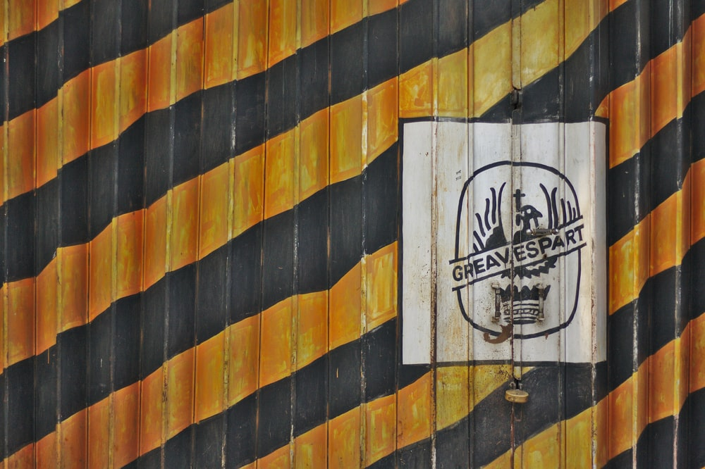 orange and black striped Greavespart painted wall at daytime